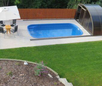 Soukromý domácí bazén Malorka se žlutým stolkem, posekaným trávníkem a labutí.