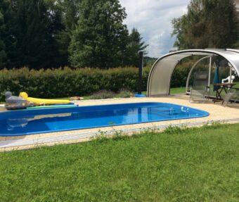 Bazén obložený dlažbou s trávou kolem, barevné lehátko do bazénu, vysoké zastřešení