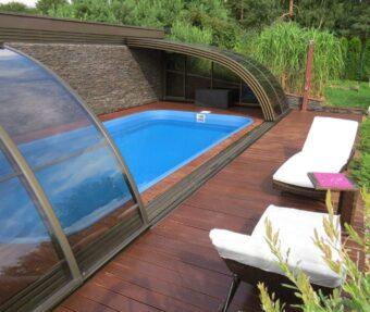Bazén Havai obložený kamenem s dřevěnou podlahou a béžovými lehátky