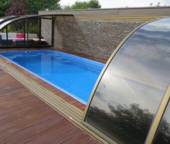 Modrý bazén se zastřešením s horní kolejnicím, obložený kamenem