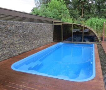 Zapuštěné schody v modrém bazénu Havai s dřevěnou podlahou