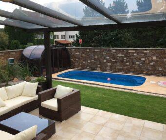 Bazén Malorka v rohu zahrady s přístupem z domu, protiproudem a lehátky.