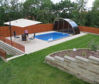 Koupací zóna bazénu Malorka s posezením, deštníkem a labutí.