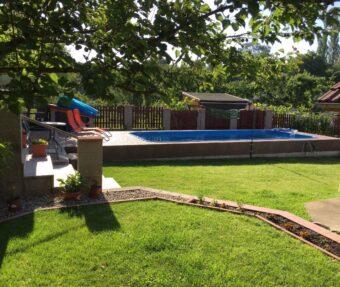 Bazén v kaskádovité zahradě se zeleným trávníkem